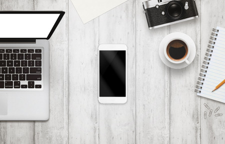 table top: White smart phone with isolated screen for mockup on office desk. Laptop, camera, cup of coffee, paper, notepad, pencil on white table. Top view.