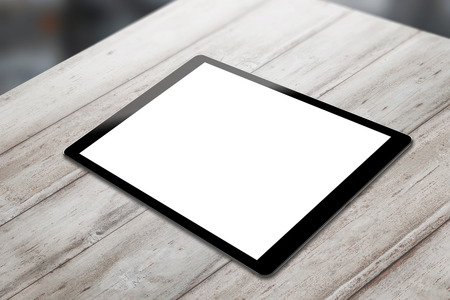 horizontal position: Black tablet on wooden table with isolated white screen for mockup. Horizontal position isometric view. Stock Photo
