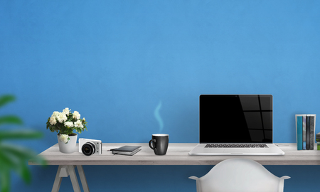 office desk: Laptop with blank screen on office desk. Free space on wall for text. Blue wall in background.