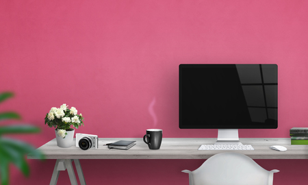 Computer with blank screen on office desk. Free space on wall for text. Pink wall in background. 版權商用圖片