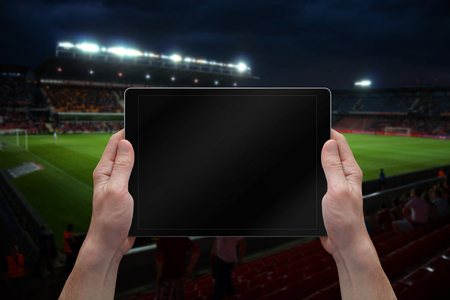 tablet: Man holding tablet with blank screen on soccer game. Stadium in background.
