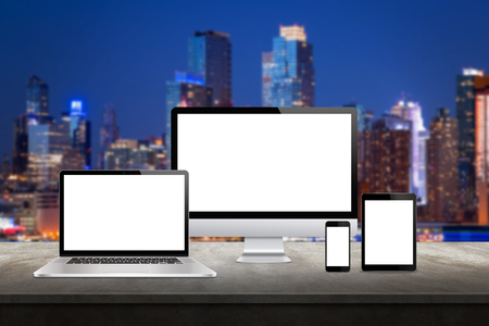 Computer display, laptop, tablet and smart phone responsive display devices on table. Isolated white screen for mockup presentation. Cityscape in background