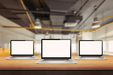 computer screens: Three laptop devices on table in office interior. Isolated white screen for mockup presentation Stock Photo