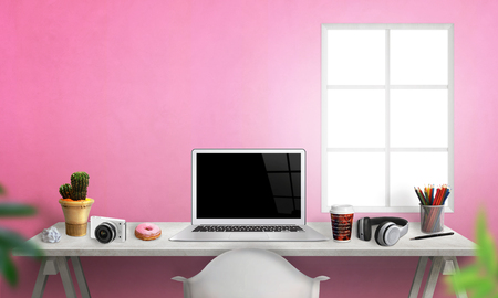 Laptop on office desk. Plant, camera, paper, pens, coffee, donut, headset on table. Pink wall in background. 版權商用圖片