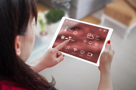 女性は、タブレットのスマート ホーム コントロールのアプリケーションを使用します。バック グラウンドでのリビング ルームのインテリア。 写真素材