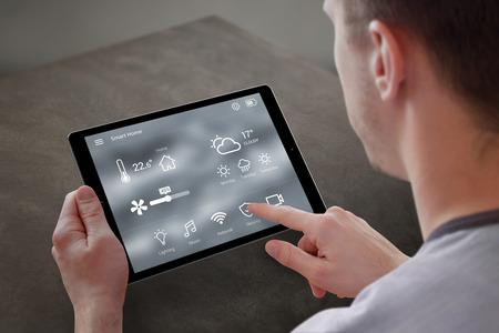 男は、タブレットのスマート ホーム コントロールのアプリケーションを使用します。バック グラウンドでのリビング ルームのインテリア。