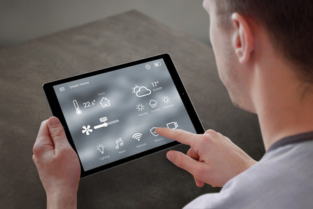 Man use application for smart home control on tablet. Interior of living room in the background. Reklamní fotografie