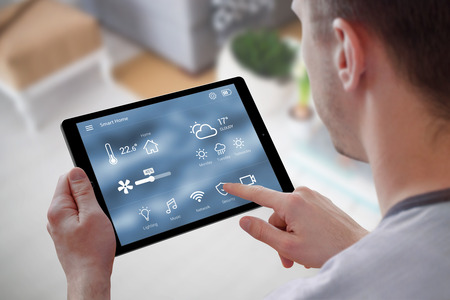 Smart home control on tablet. Interior of living room in the background. Stock Photo