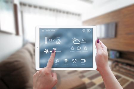 Smart home control on tablet. Interior of living room in the background. Reklamní fotografie