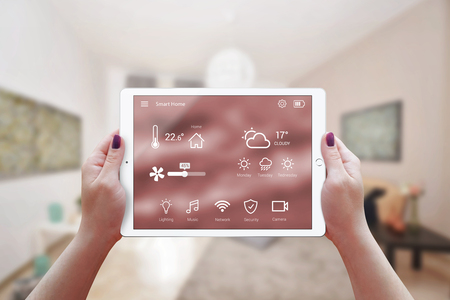 Smart remote home control app in woman hand. Living room interior in background.