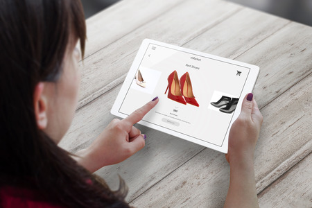 Shopping with tablet. Woman buy red shoes on online market. 版權商用圖片