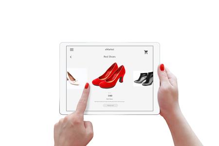 孤立したタブレットと女性の手オンライン ショッピングします。デバイスを保持し、赤い靴を選択します。 写真素材