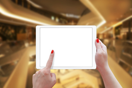 blank tablet: Woman holding tablet in shopping center. Isolated screen for mockup. Stock Photo