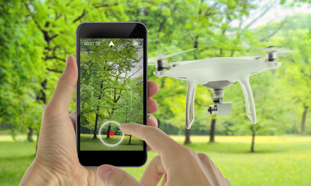 Smart phone control drone with app. Park in background.