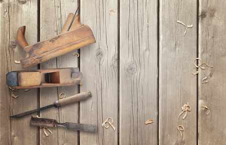 Wood planer and chisel on wooden desk.