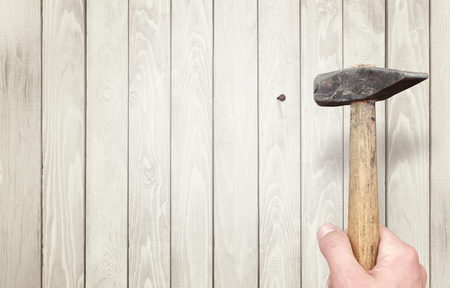 hammering: Hammering nail  in wooden surface. Stock Photo