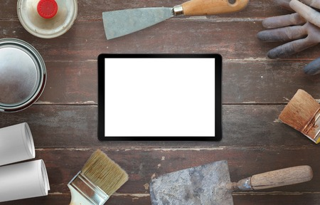 Tablet and tools for house renovation. Top view on wooden desk. Stock Photo