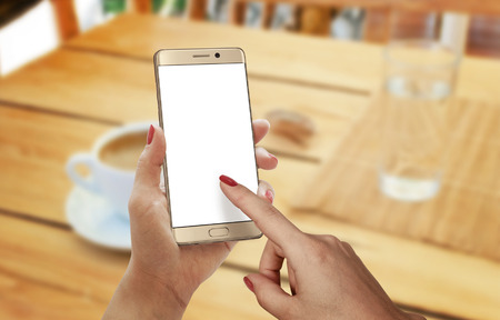 caffee: Coffee time with smart phone. Device with isolated display for mockup in woman hand.