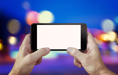 horizontal position: Use camera or play game on mobile phone with isolated display mockup. Phone in hands, horizontal position. City, night lights in background.