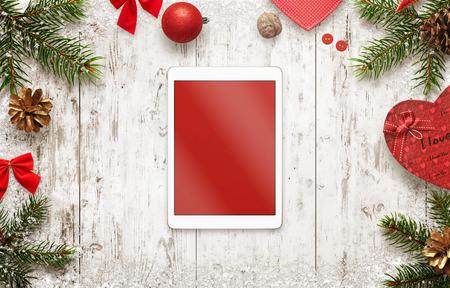 テーブルの上のクリスマスの装飾とモックアップの分離スクリーンを搭載したタブレットします。クリスマス ツリーとギフトで白い木製のデスクの