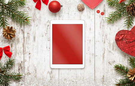 Tablet with isolated screen for mockup with christmas decorations on table. Top view of white wooden desk with christmas tree and gifts.