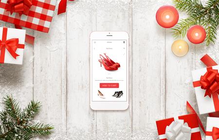 comprando zapatos: compras de Navidad con el teléfono inteligente. La compra de zapatos en línea sobre el comercio sitio web o aplicación. decoraciones y regalos de Navidad al lado.