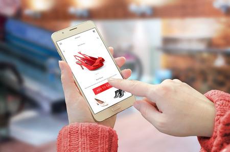 Aplicación de sitio web de compras en teléfonos inteligentes. Mujer sosteniendo el dispositivo móvil y comprar zapatos rojos. Centro comercial de la ciudad en el fondo. Foto de archivo