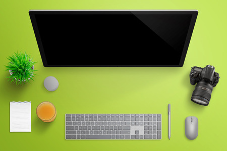 Photographer studio with big computer display. Modern surface studio with keyboard, pen, mouse, and dial. Digital camera, plant, juice and pad beside. Top view. Green desk background.
