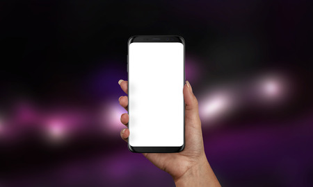 Woman holding black modern smartphone with isolated screen for app or web site presentation. Product mockup. Purple bokeh in background. Stock Photo