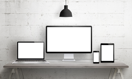 Responsive web site mockup. Computer display, laptop, tablet and smart phone on desk with isolated, blank, white screen for design presentation.