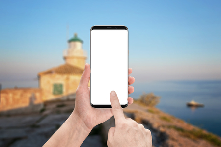 blank screen: Woman touch modern smart phone screen. Isolated display for mockup with round edges. Lighthouse and sea in background.