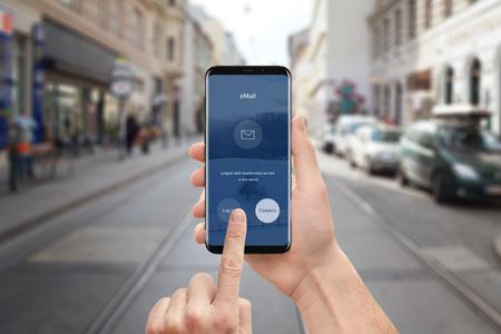 남자는 휴대 전화에서 이메일 응용 프로그램을 사용합니다. 둥근 모서리와 평면 사용자 인터페이스 디자인이 적용된 최신 스마트 폰. 백그라운드에서