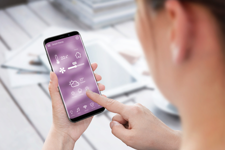 Woman use smart home control app on mobile phone. Stock Photo