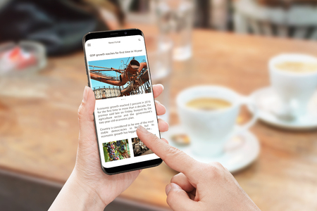 Read news article with smart phone. News portal web site with business information. Economic growth article. Coffee on table in background. Stock Photo