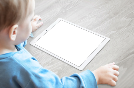 Baby with pacifier watching tablet with isolated screen for mockup.