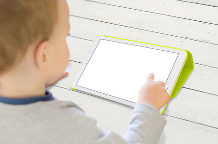 Boy use tablet on white wooden desk. Isolated white, blank screen for app mockup.