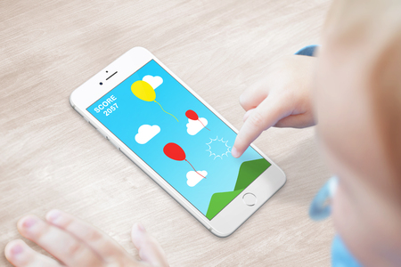 Baby play game on modern smart phone. Easy kids game with drilling balloons.