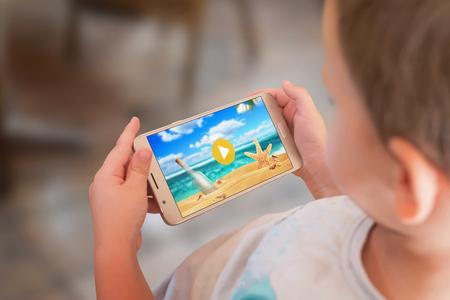 Niño está viendo una caricatura en un teléfono móvil. Foto de archivo - 86957101