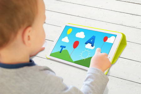 Child play game with letters on a tablet. Modern app for developing childrens abilities. 版權商用圖片