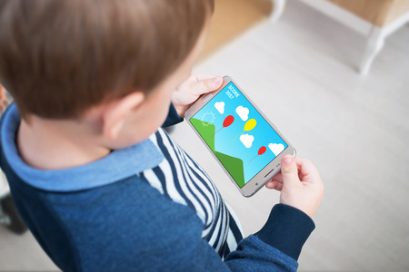 Boy play game on smart phone. Creative applications for children stimulate thinking.