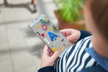 Boy agrees letters on a mobile app and learn through the game.