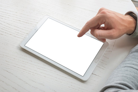 Tablet op wit houten bureau. Schermmockup. Rechterhand aanraakscherm. Stockfoto