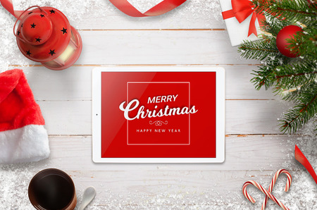 Merry Christmas greeting card with tablet, Christmas tree, gifts and decorations. Top view with white wooden desk in background.