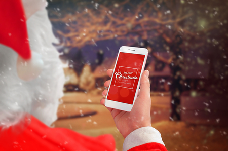 Santa Claus holding smart phone with Merry Christmas massage. Winter and snow outdoor in background. Stock Photo