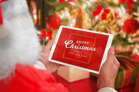 Santa Claus holding tablet with Merry Christmas greeting massage. Christmas tree with gifts, lights and decorations in background. Stock Photo