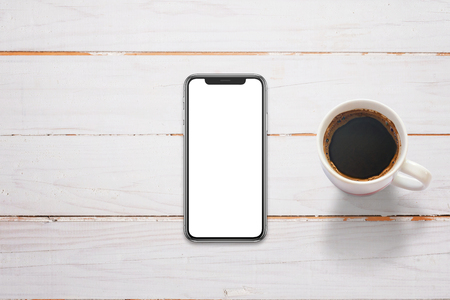 Mobile phone with x screen on white wooden table. Cup of coffee beside. Top view.