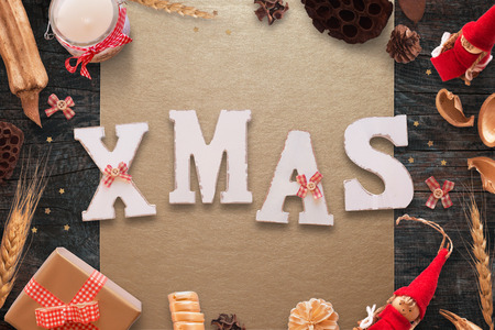 Xmas white wooden text on wooden table surrounded with Christmas decorations. Stock Photo