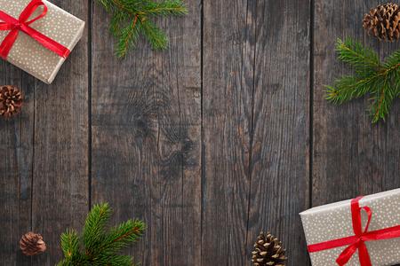 クリスマスの贈り物、モミの枝と黒い木のテーブルの上の松ぼっくりと背景。平面図です。