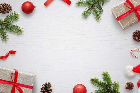 White table with Christmas decorations and space in the middle for text. Christmas composition with gifts, fir branches, lollipop, Santa hat and pinecones. Top view. Archivio Fotografico