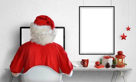 Santa Claus work on computer. Picture poster frame on wall with isolated blank space for mockup, adding greeting text. Christmas decorations on table. Stock Photo
